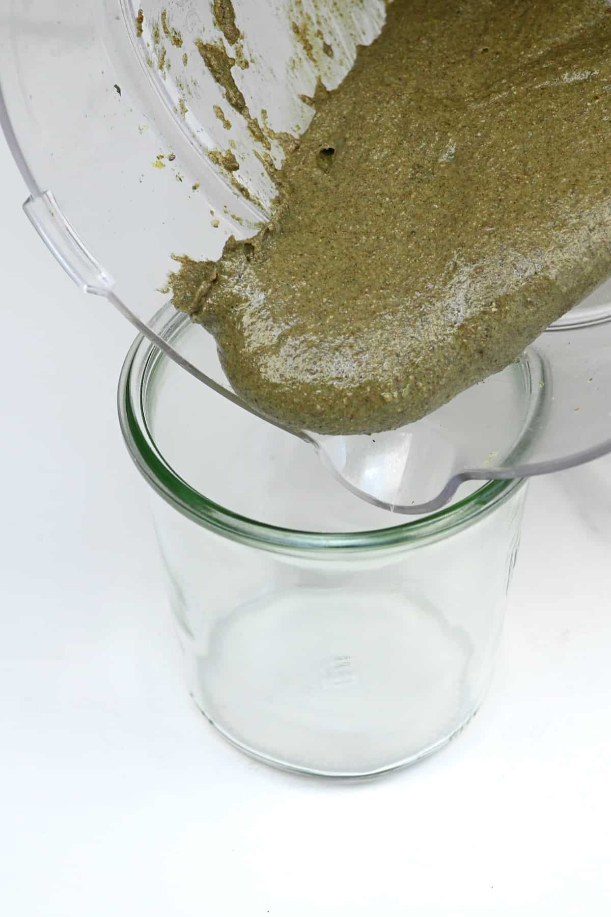 Pouring omega seed butter in a jar