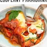 Cutting off a piece of eggplant parmigiana with a knife and fork