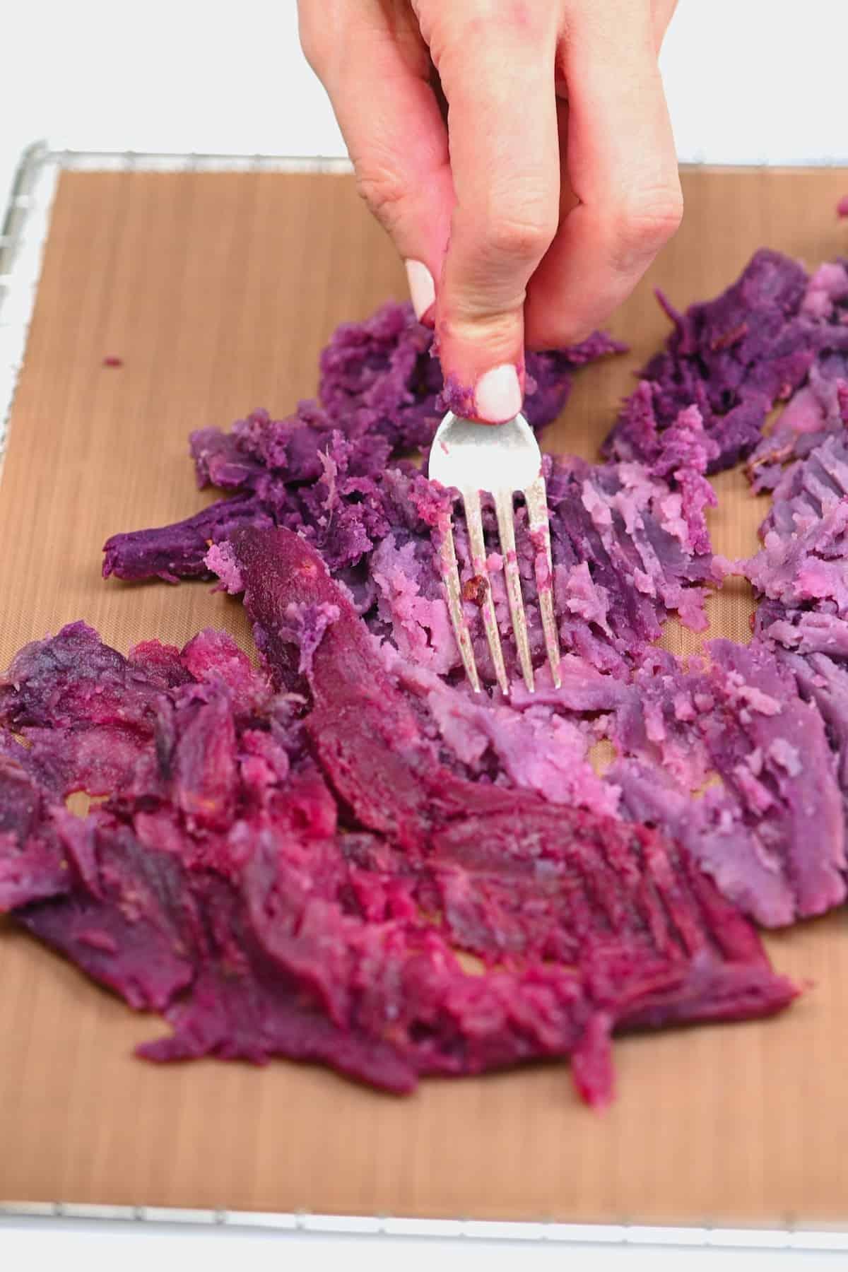 Mashing baked purple sweet potato