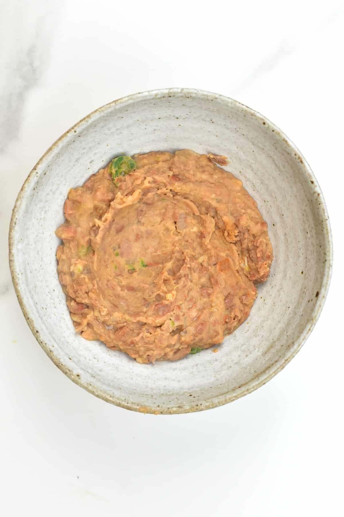 Vegan refried beans in a bowl (frijoles refritos)