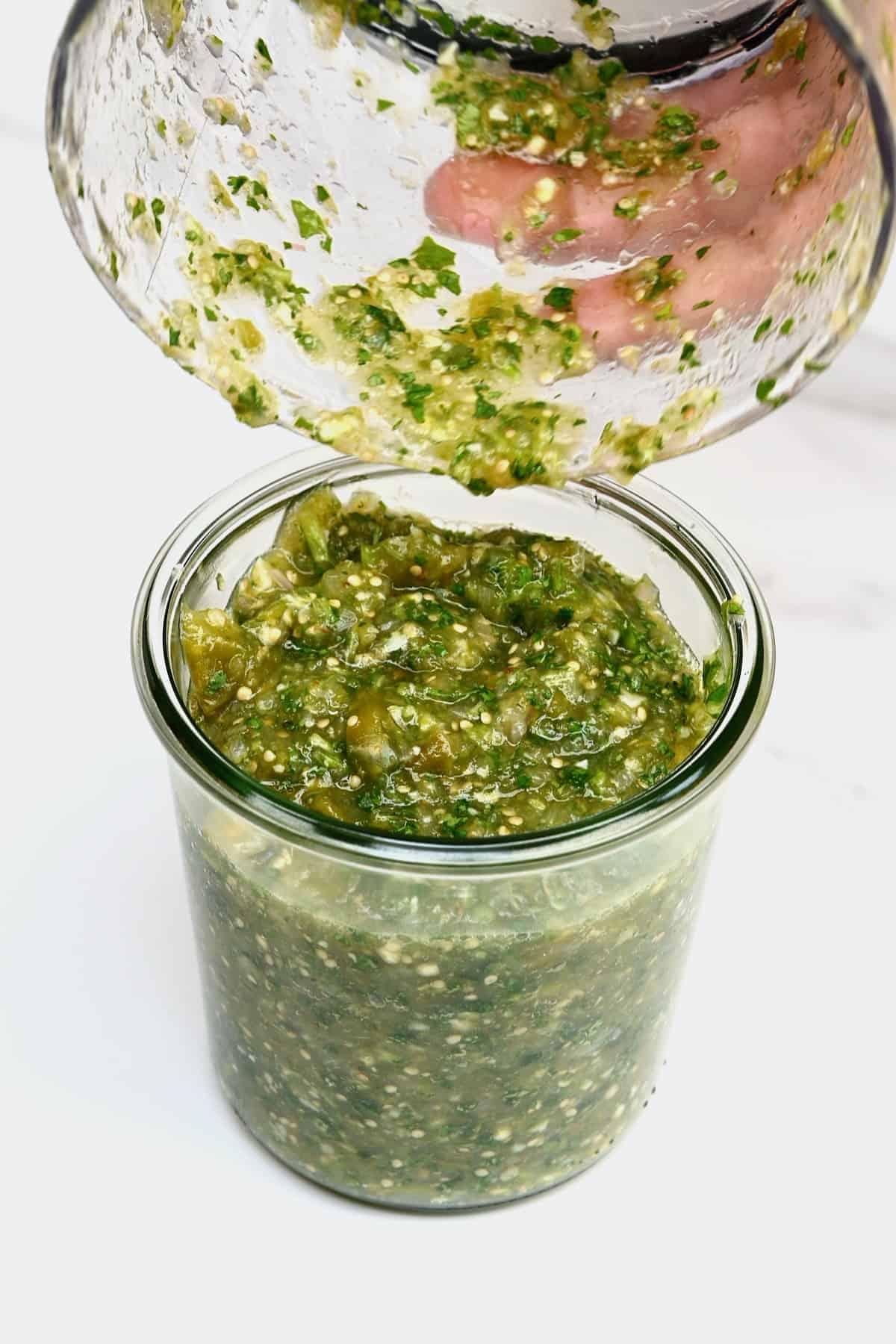 Pouring tomatillo green chili salsa in a jar