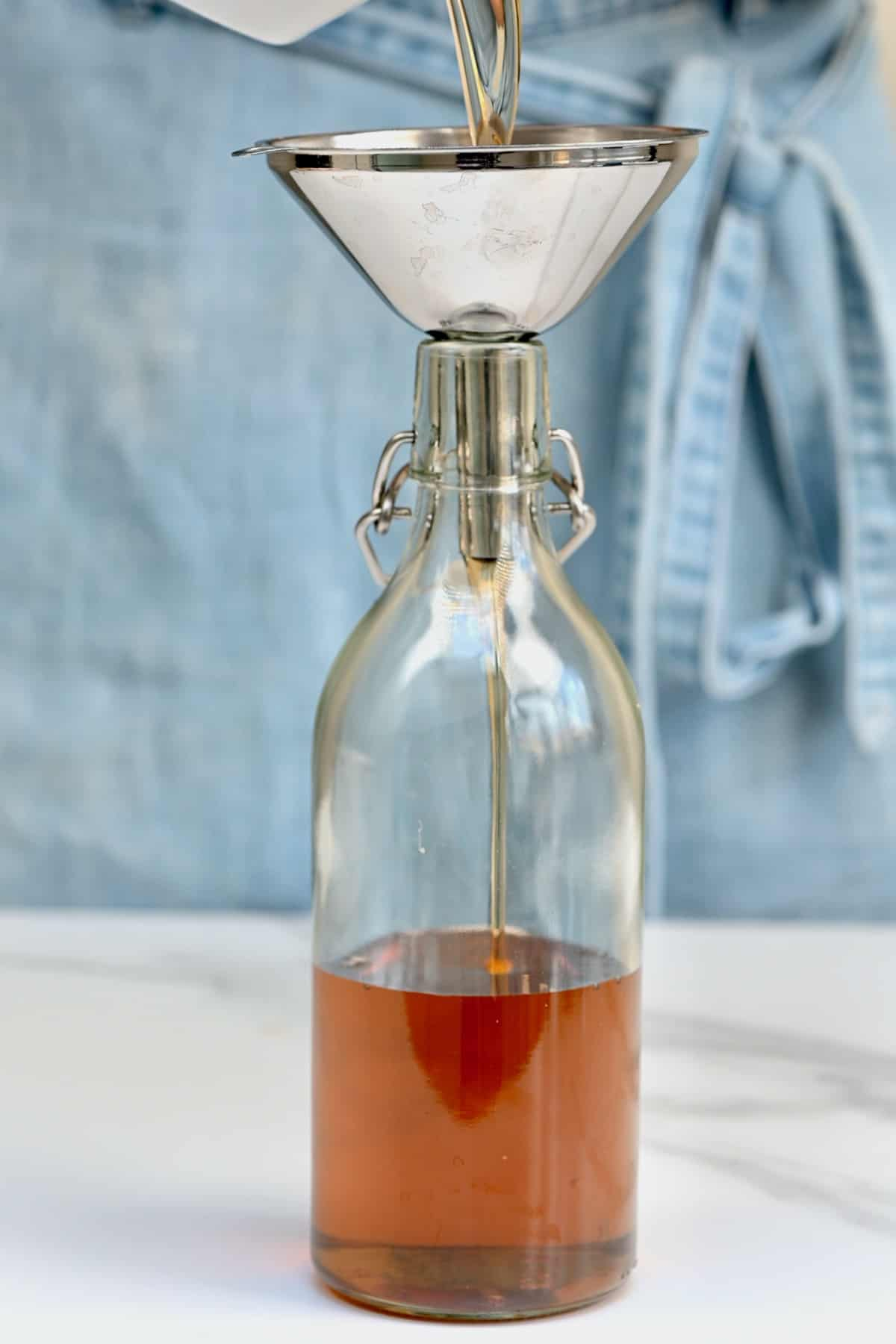 Pouring simple syrup in a bottle