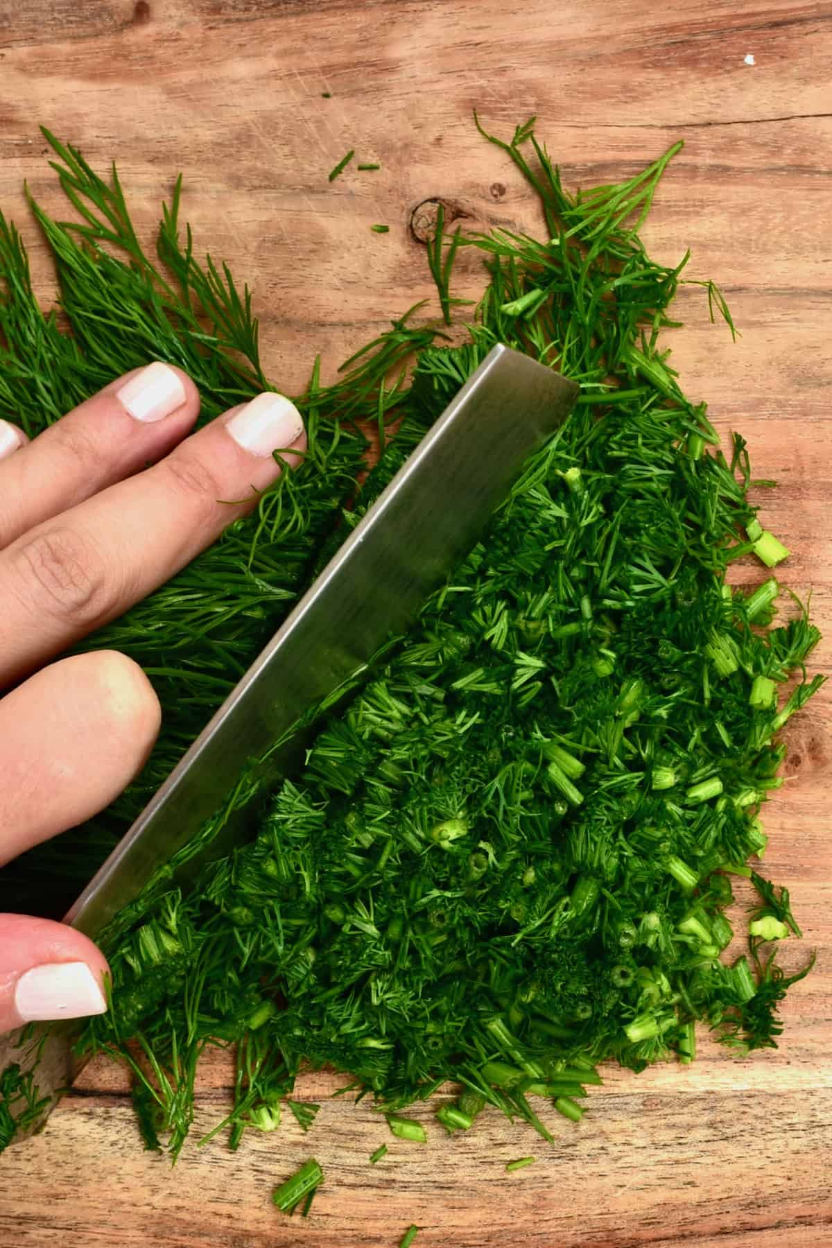 Chopping dill on a wooden board