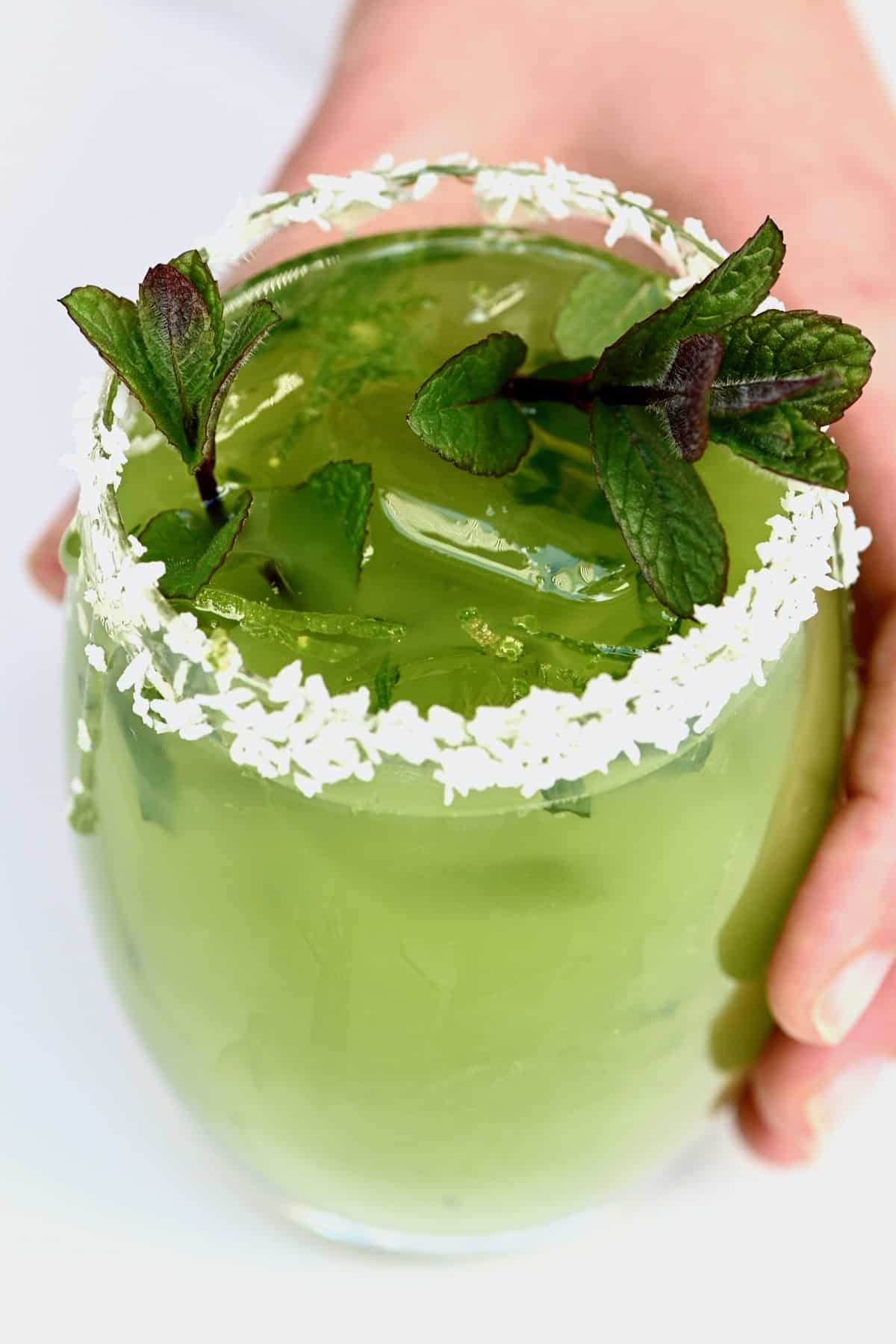 Hand holding a glass with cucumber lemonade