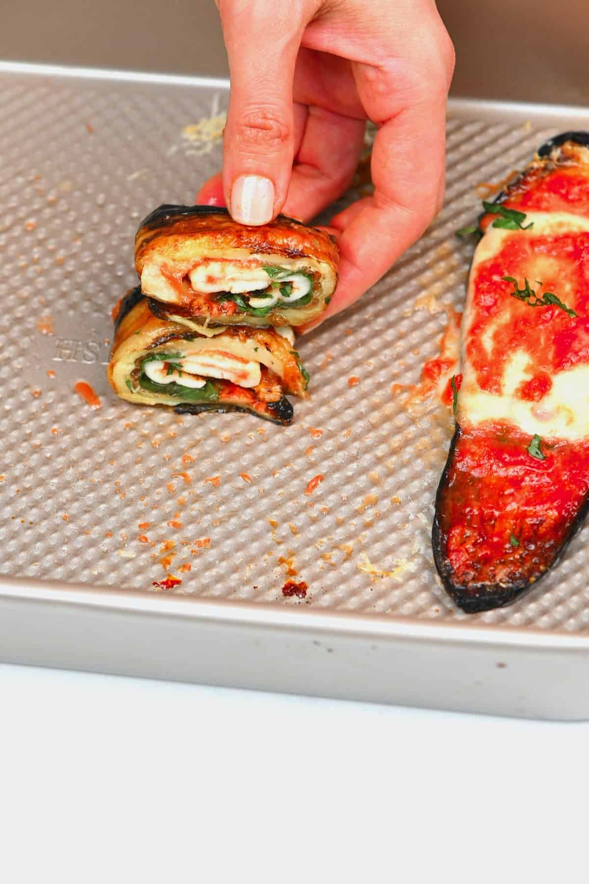 Two rolls of baked eggplant and cheese