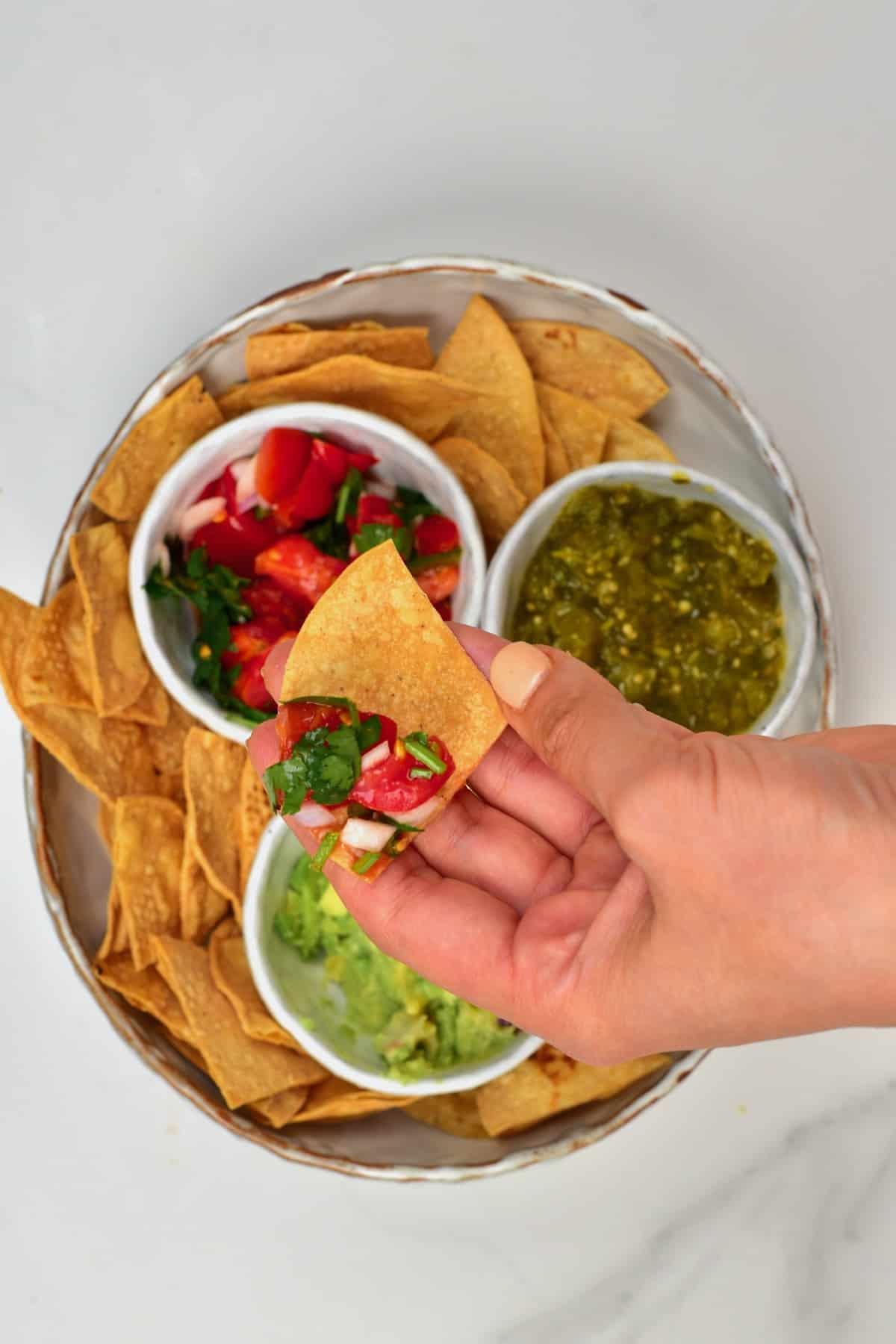 Hand holding tortilla chip with pico de gallo