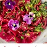 Pink beetroot pasta with basil pesto and edible flowers