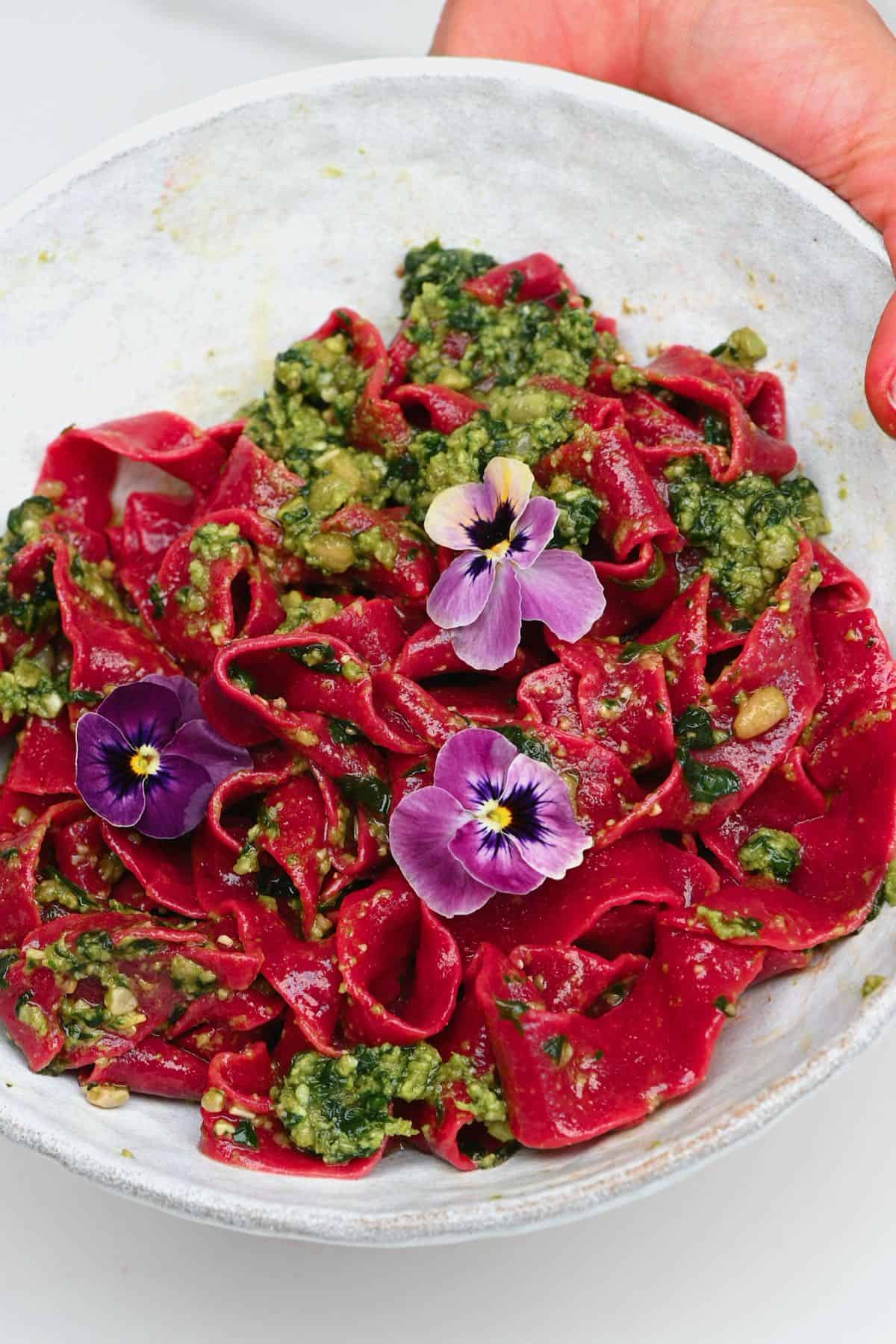 A serving of beetroot pasta basil pesto and flower decoration