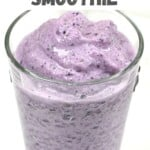 Ube and blueberry smoothie in a tall glass
