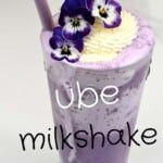 Ube milkshake in a tall glass with a straw and edible flower decoration
