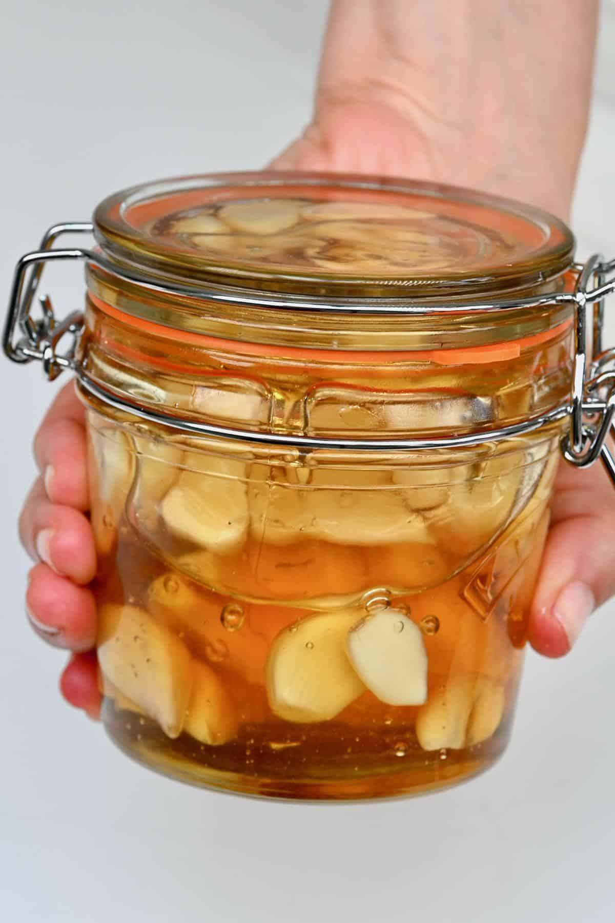 Hand holding a jar with fermented honey garlic