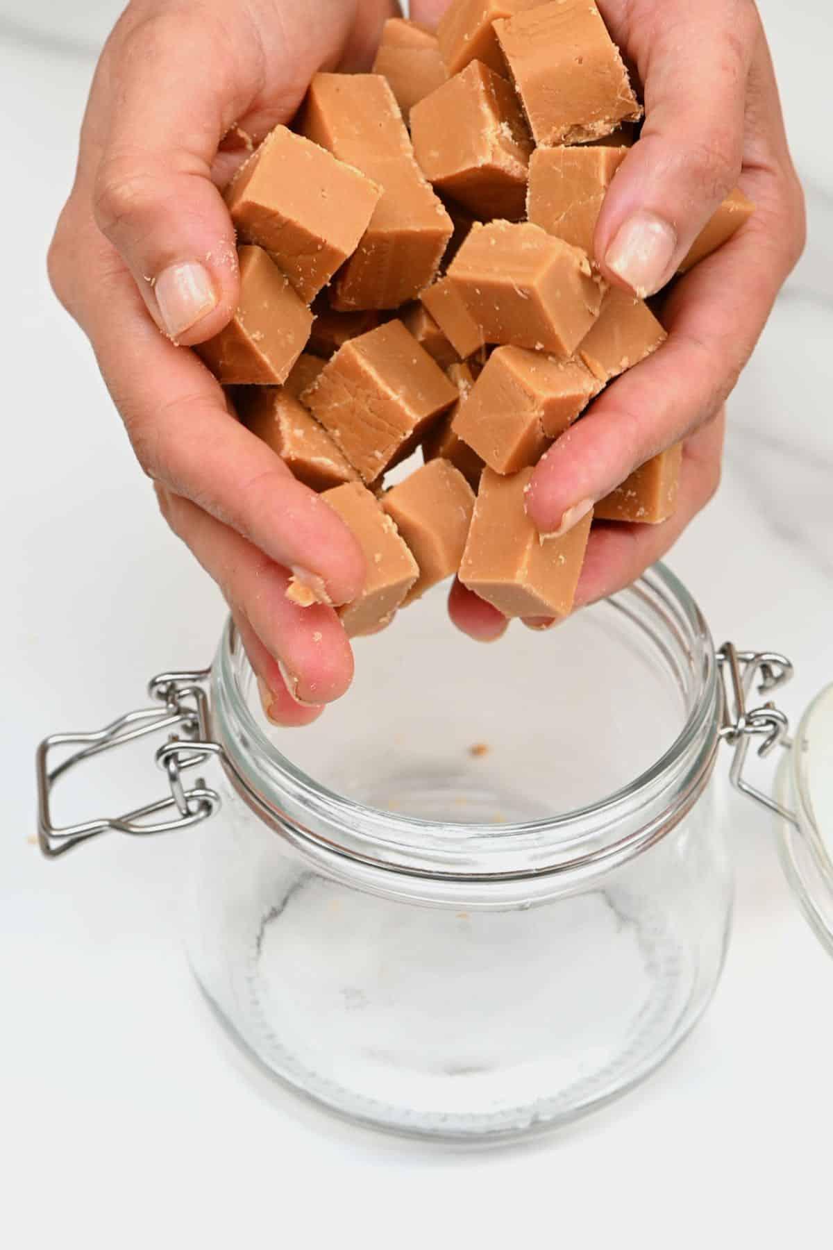 Placing homemade fudge cubes in a jar