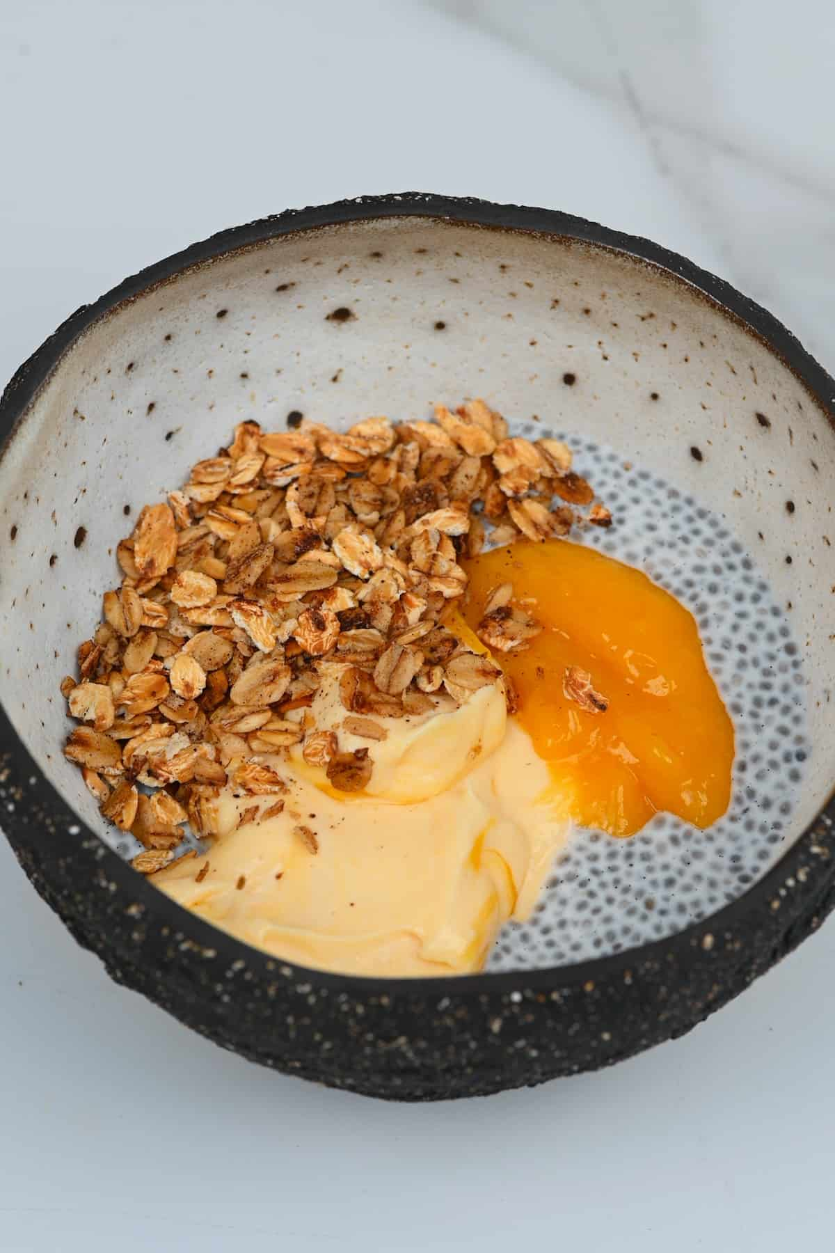 Chia pudding and mango yogurt topped with crispy oats