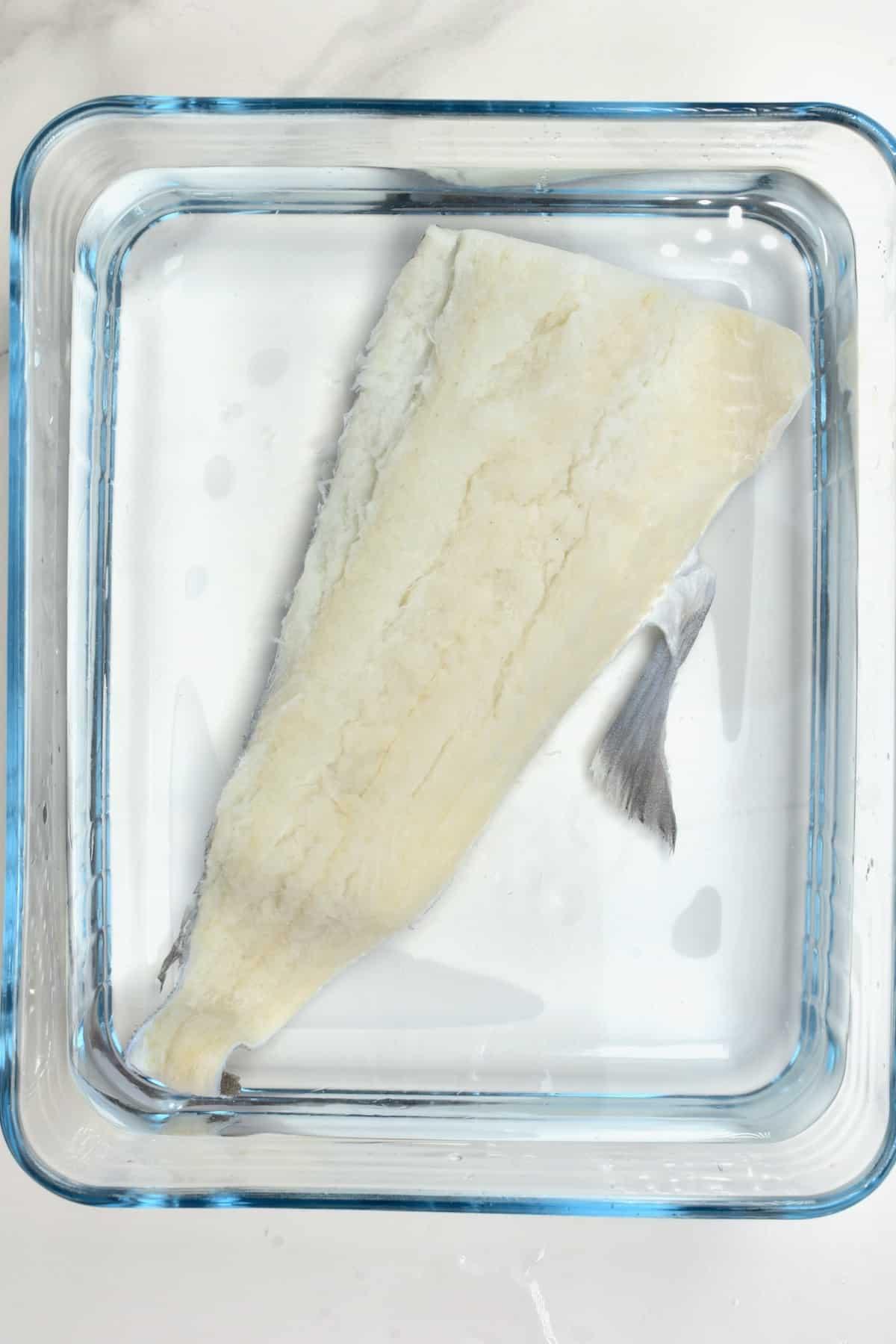 Soaking a cod fish in a bowl