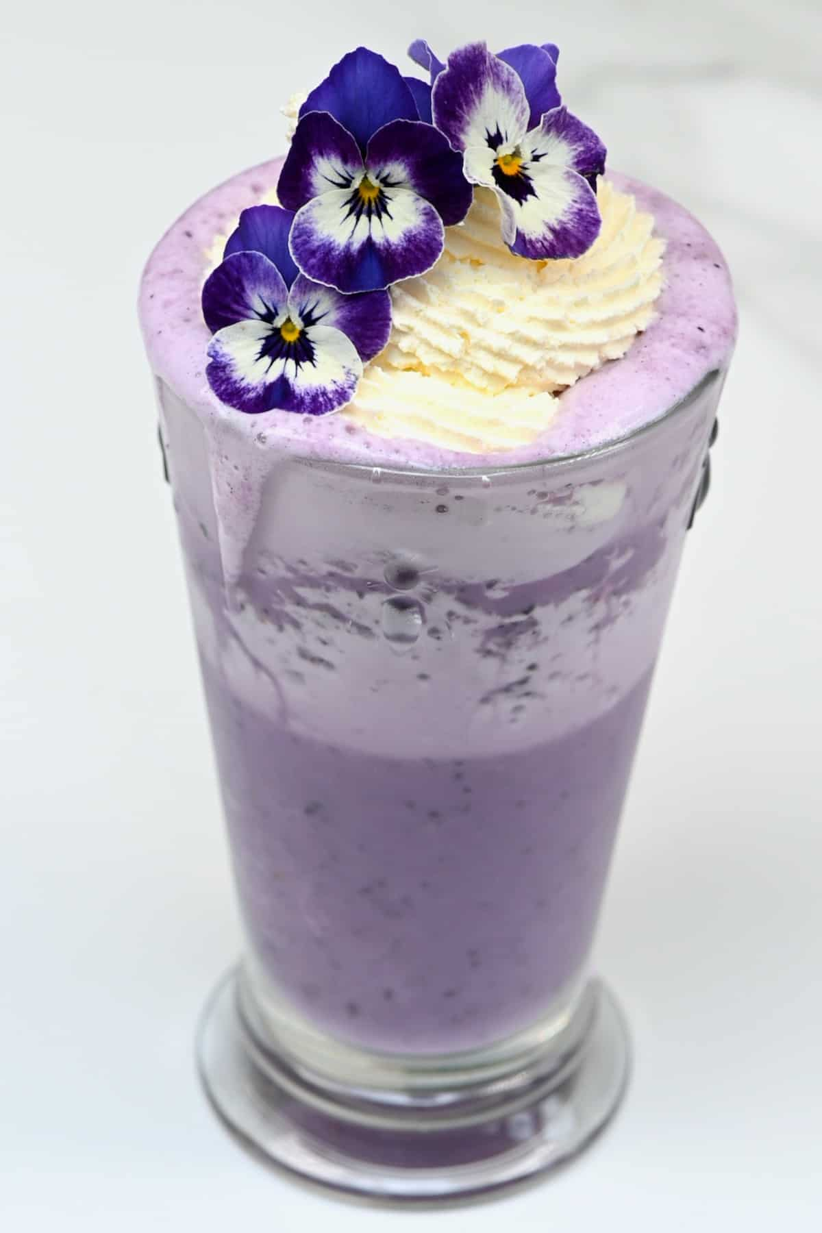Blueberry ube frappuccino decorated with edible flowers