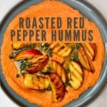Roasted red pepper hummus topped with grilled peaches and pesto
