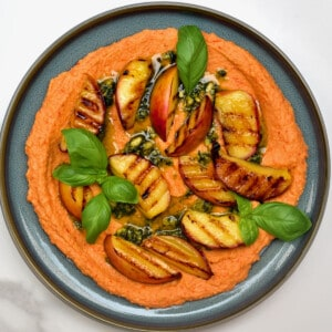 Roasted red pepper hummus topped with grilled peaches and basil