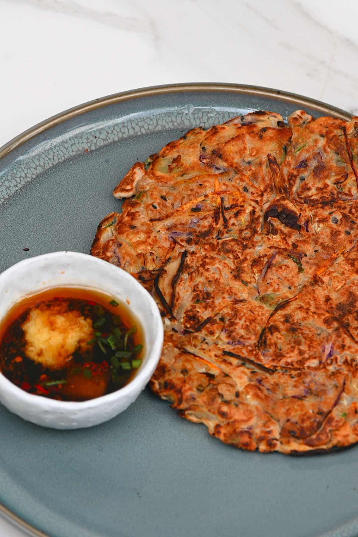 Savory pancake on a plate and a bowl of sauce