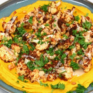 Golden turmeric hummus topped with cauliflower pine nuts and parsley