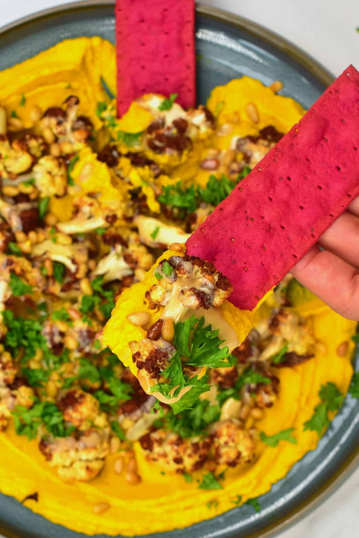 Cracker topped with turmeric hummus