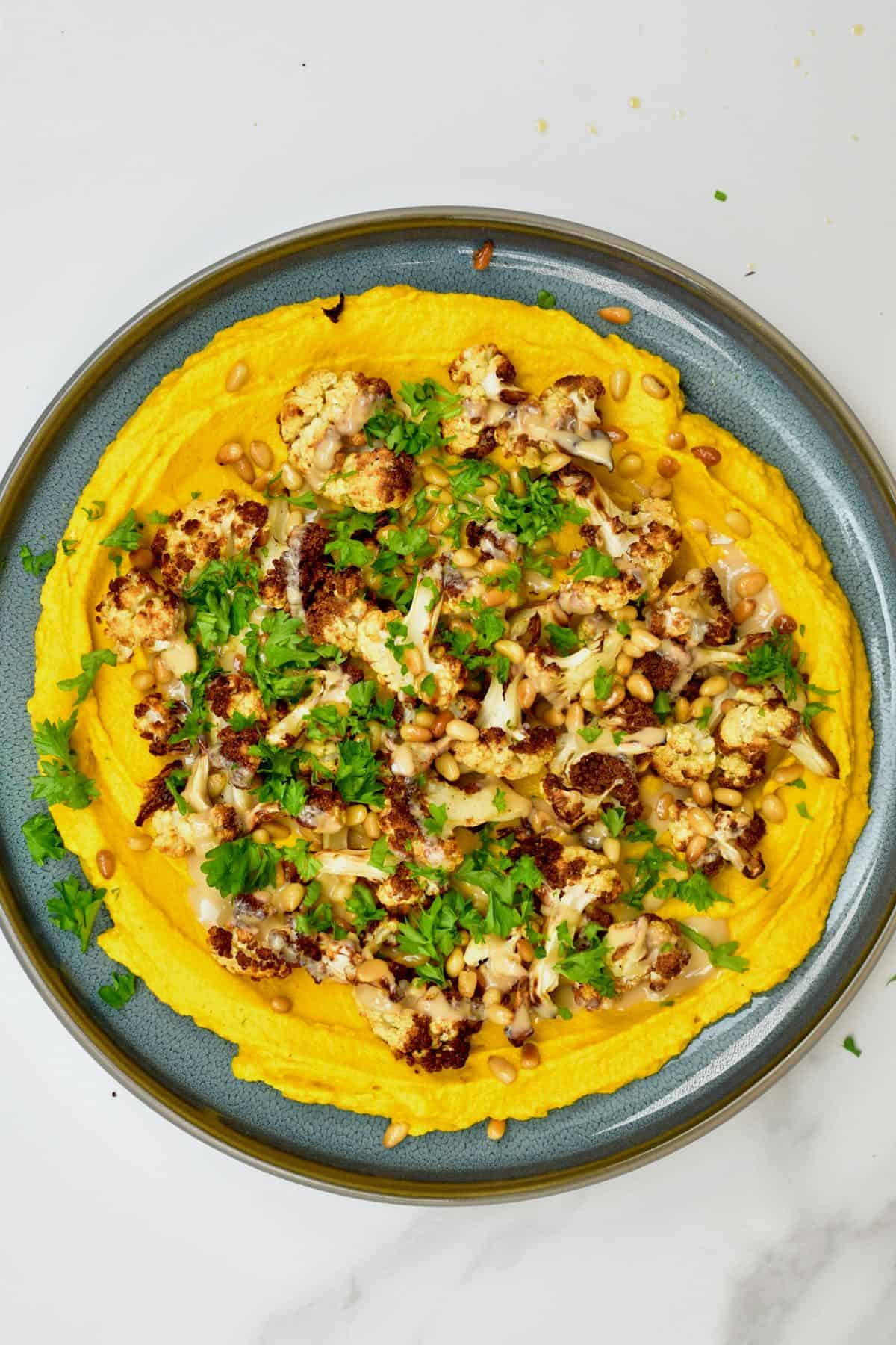 Turmeric hummus topped with cauliflower and parsley