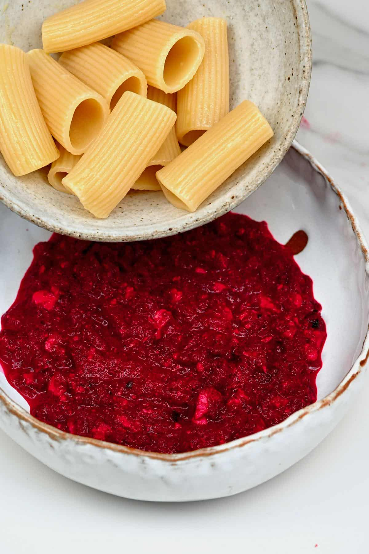 Mixing cooked pasta into beetroot pasta sauce