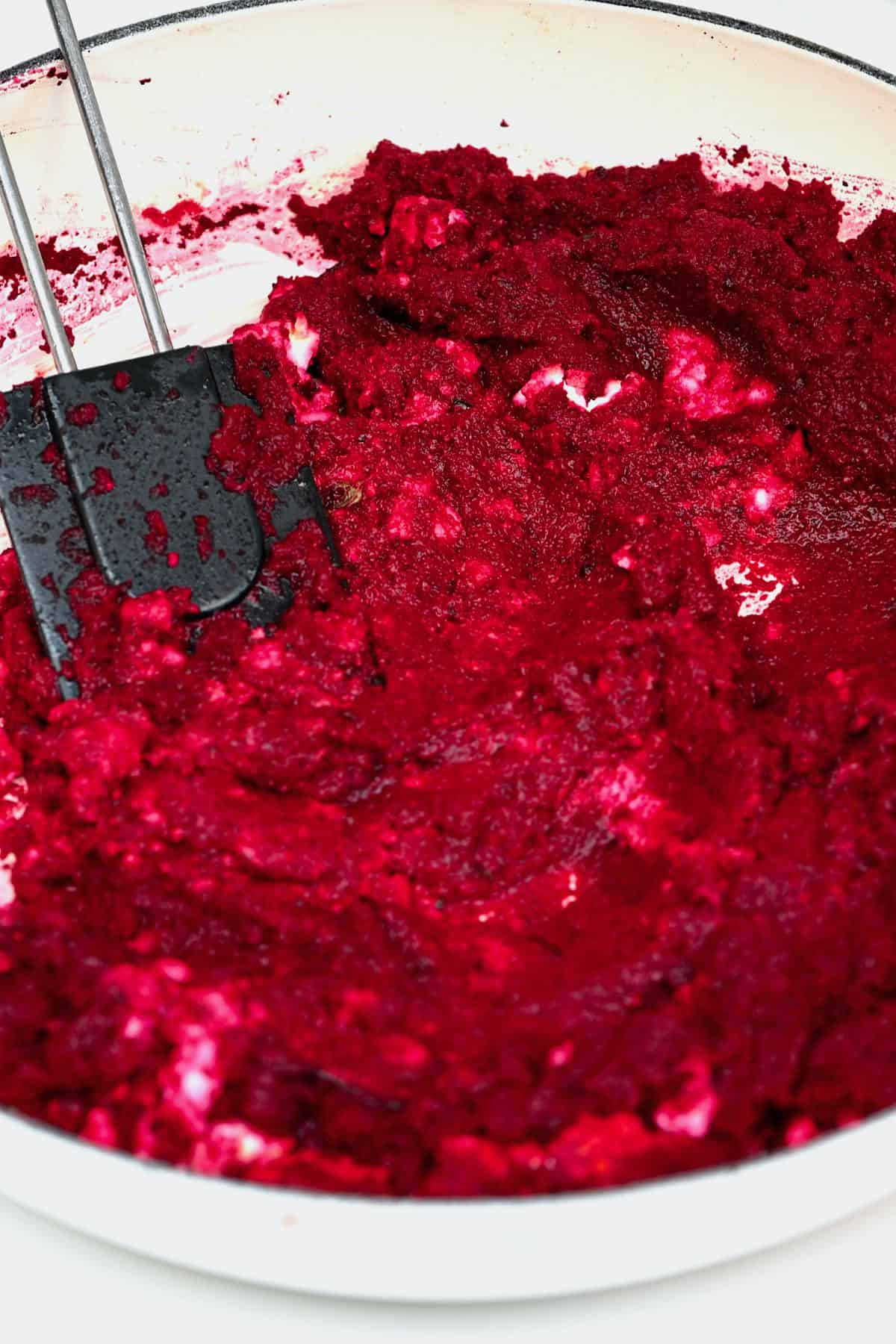 Mixing roasted beetroot with feta