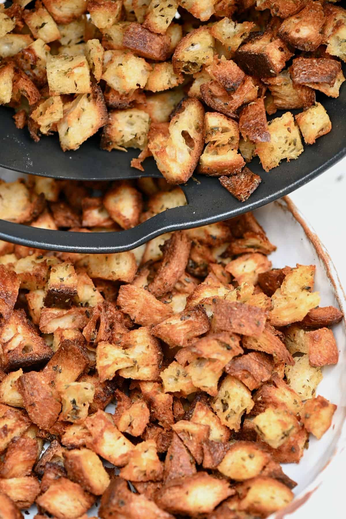 Placing homemade croutons in a bowl