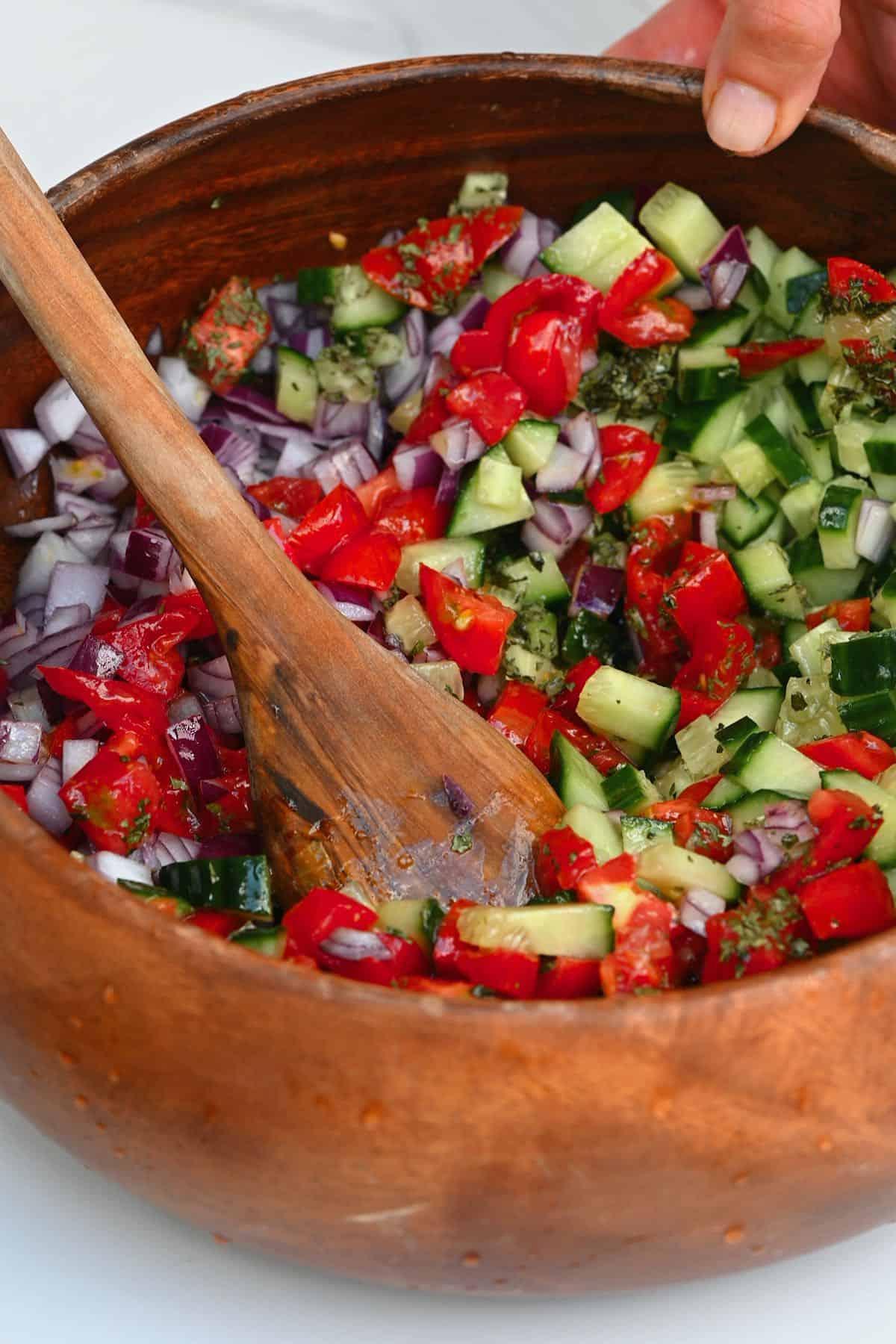 Mixing tomato cucumber salad