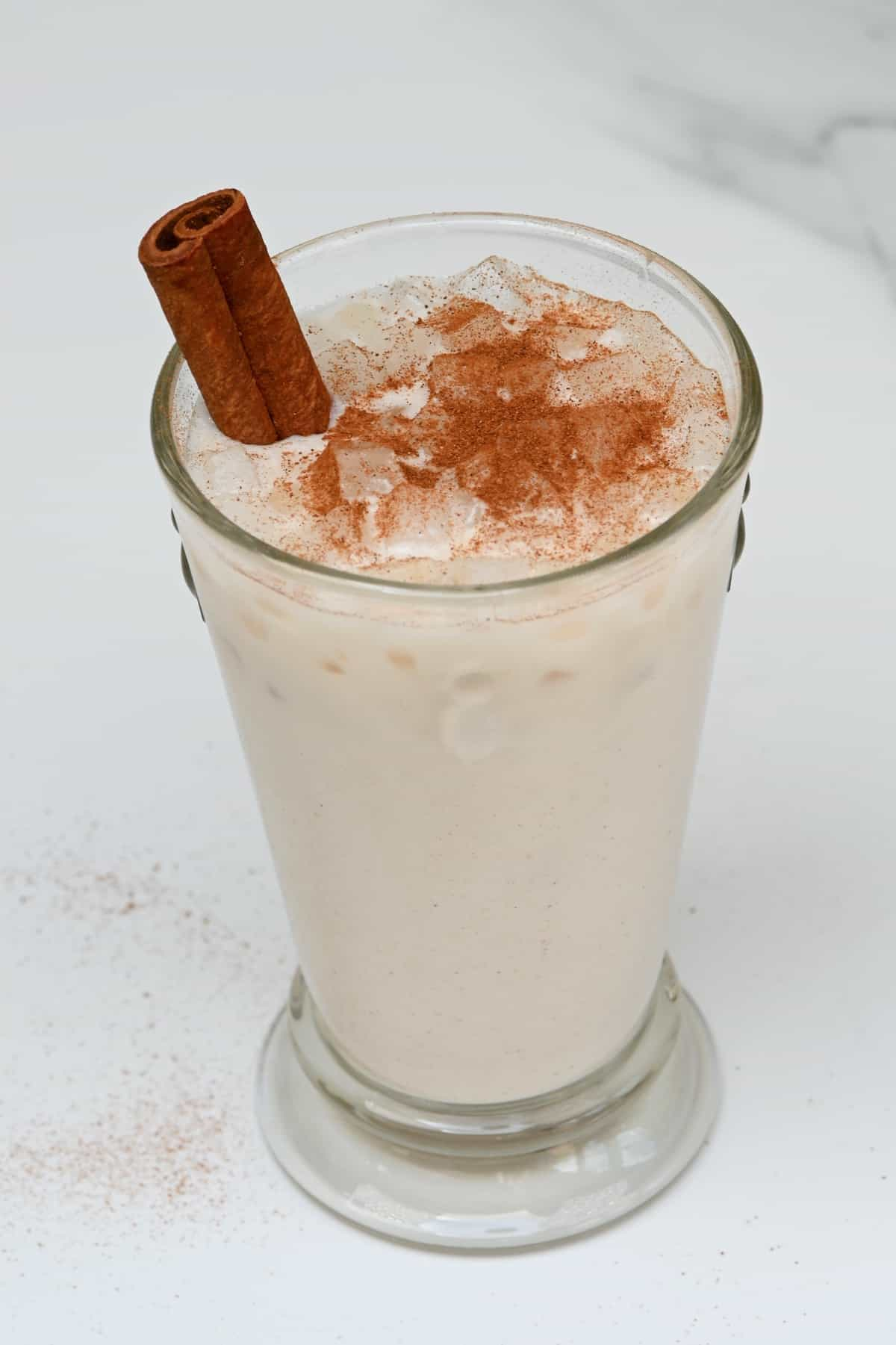 A glass with Mexican horchata topped with cinnamon powder