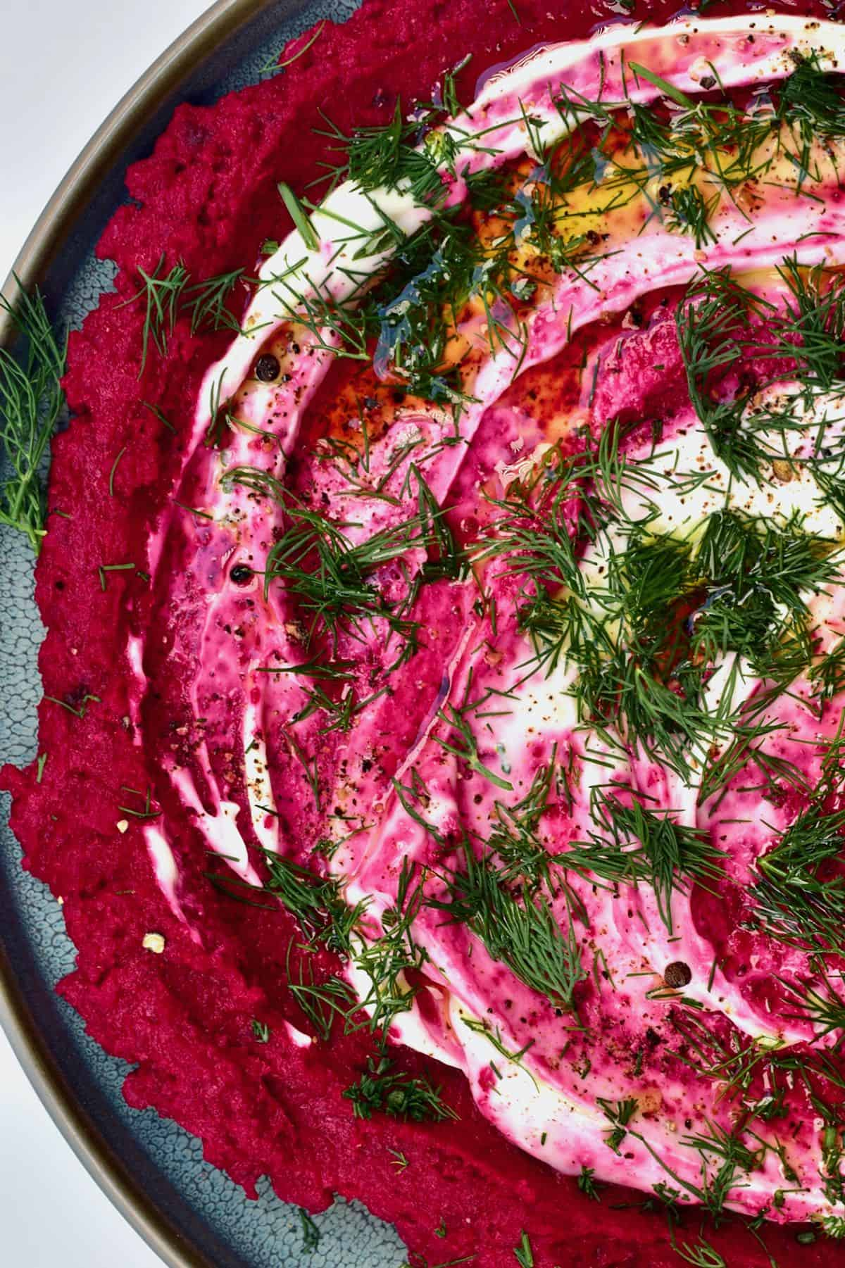 Beetroot hummus topped with whipped cheese and dill