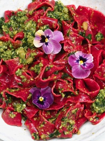 Pink beet pasta topped with pesto and edible flowers