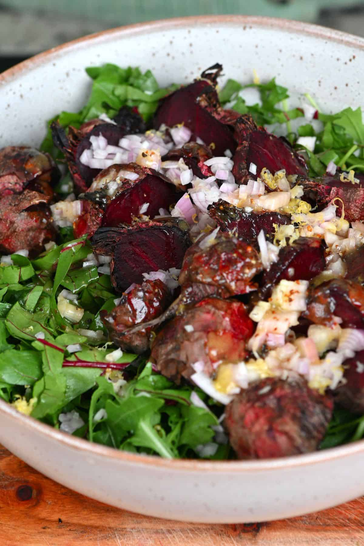 Mixing roasted beet salad in a bowl