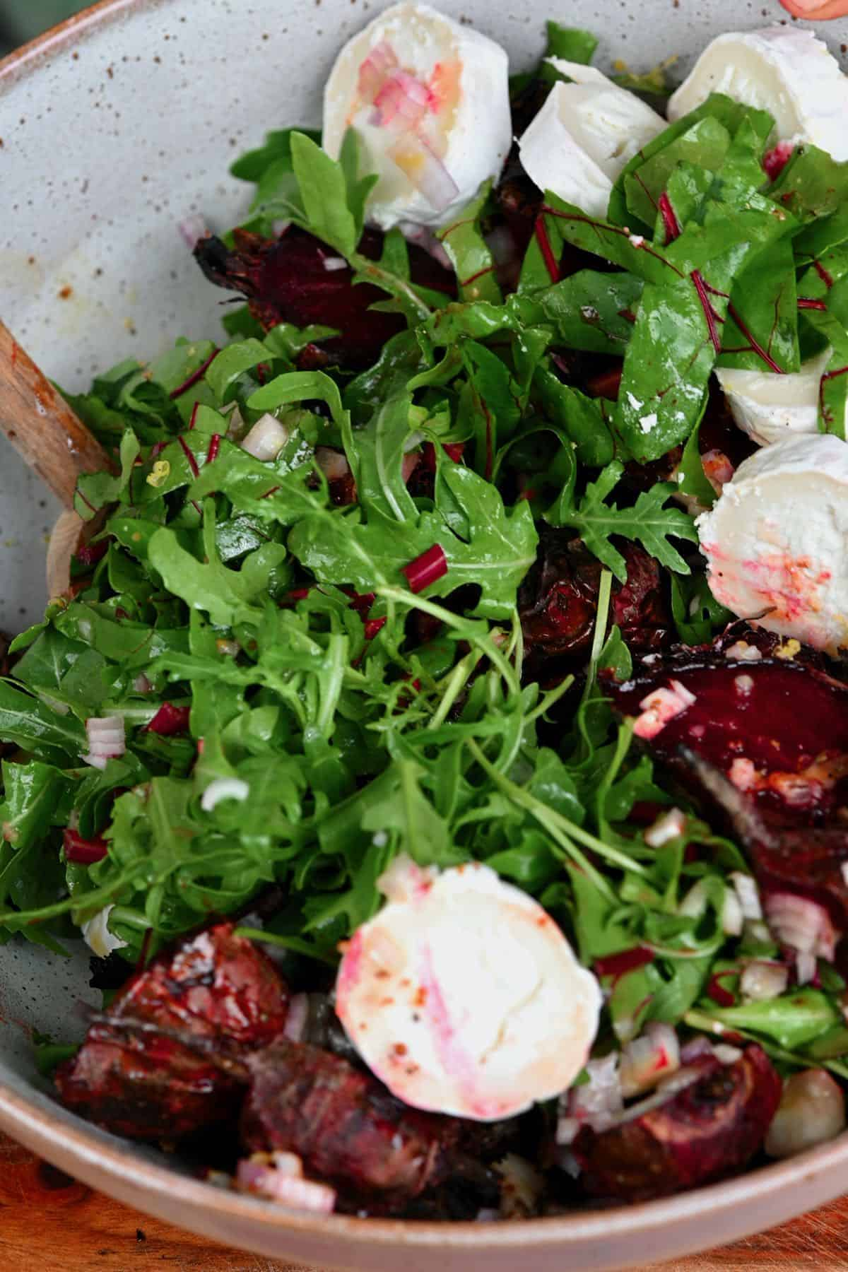 Mixing roasted beet salad with goat cheese in bowl