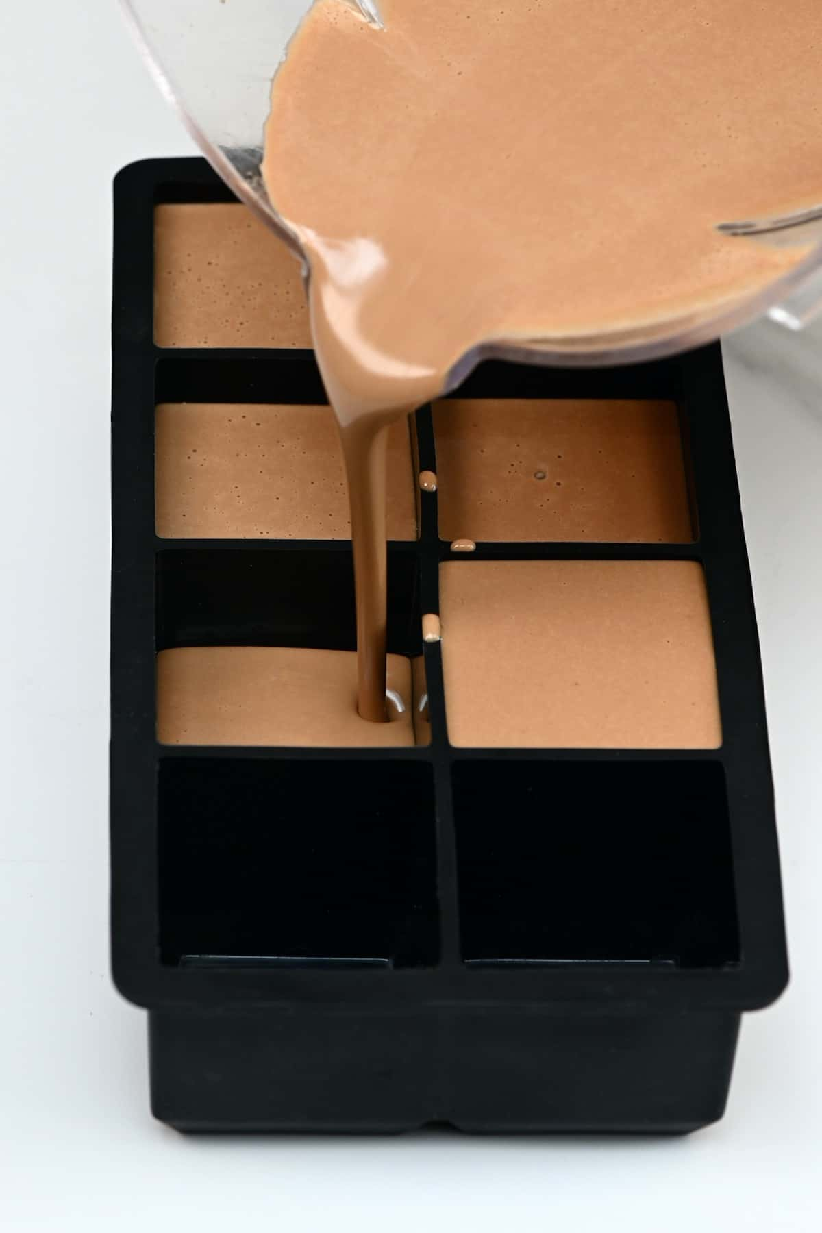 Pouring coffee ice cream in ice cube tray