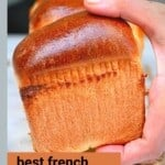 Hand holding a piece of brioche loaf