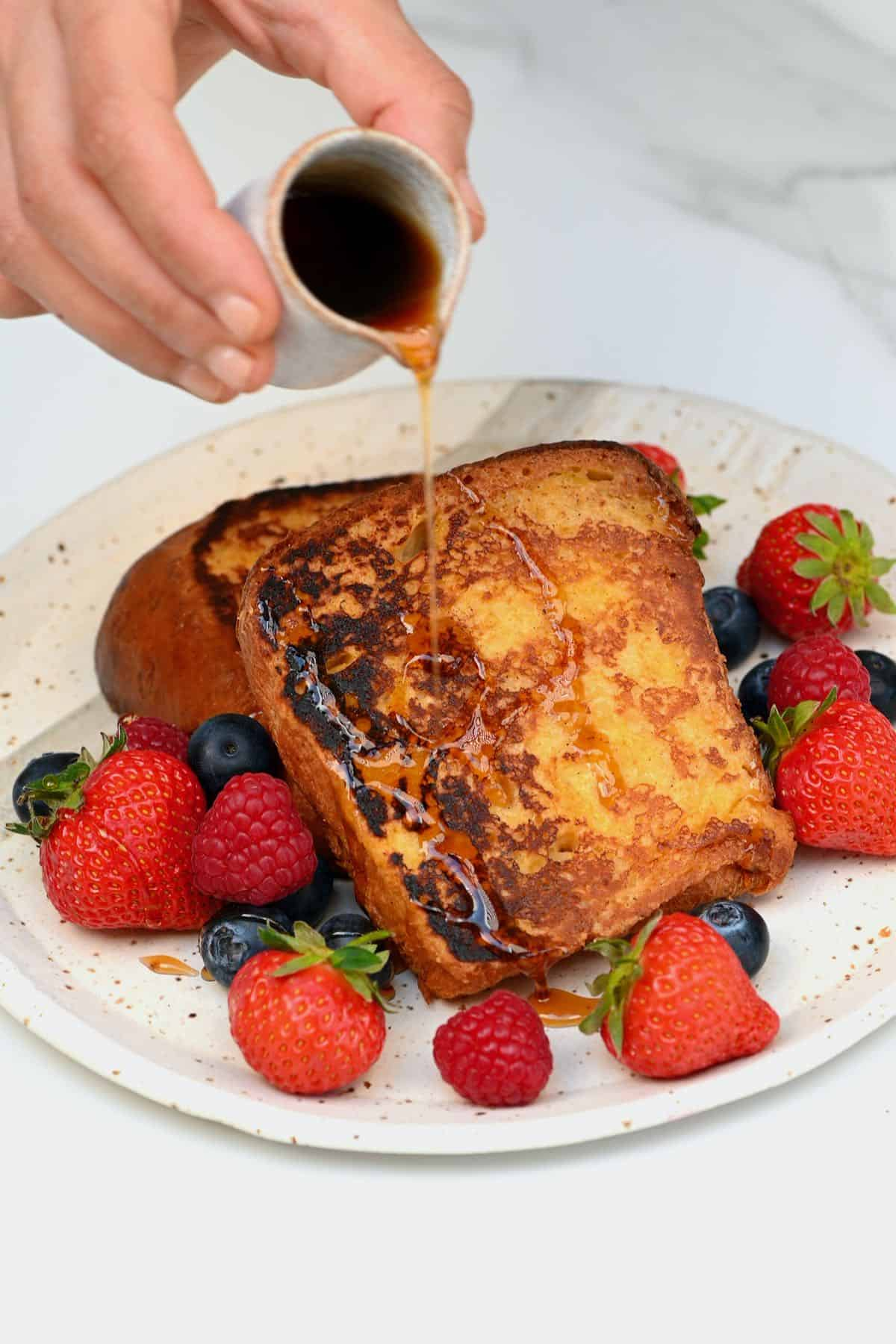 Pouring maple on brioche French toast