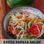 Green papaya salad in a bowl with a papaya behind it