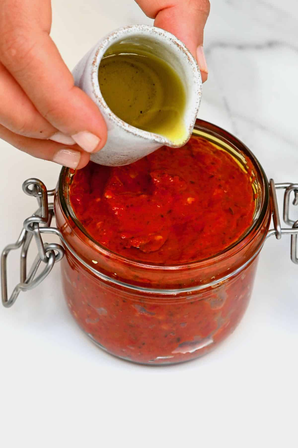 Adding oil to harissa in a jar