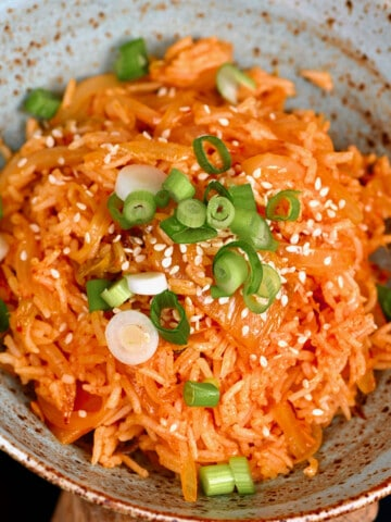 Kimchi rice topped with green onion in a bowl