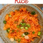 A bowl with kimchi fried rice topped with green onions