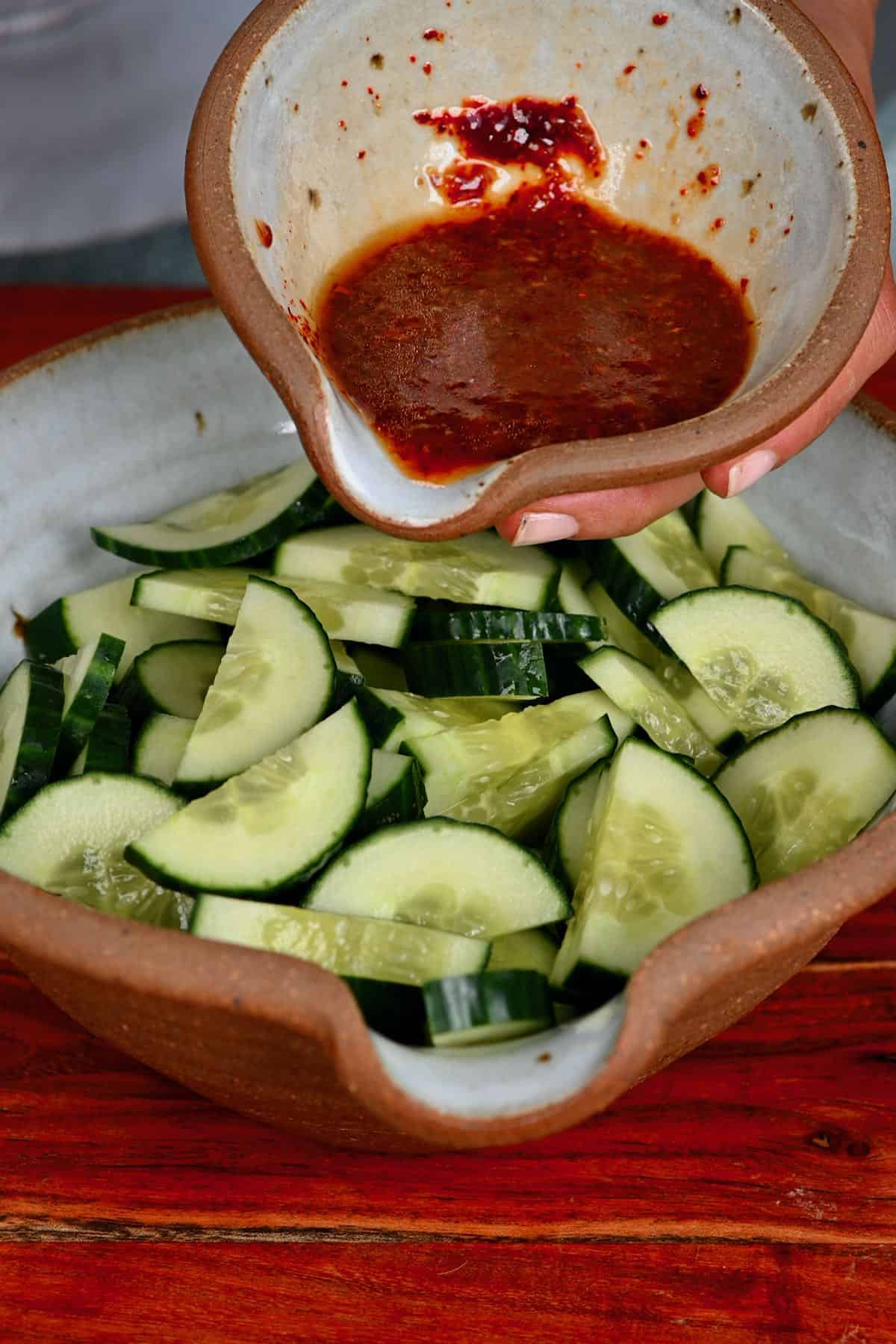 Pouring dressing over cucumbers