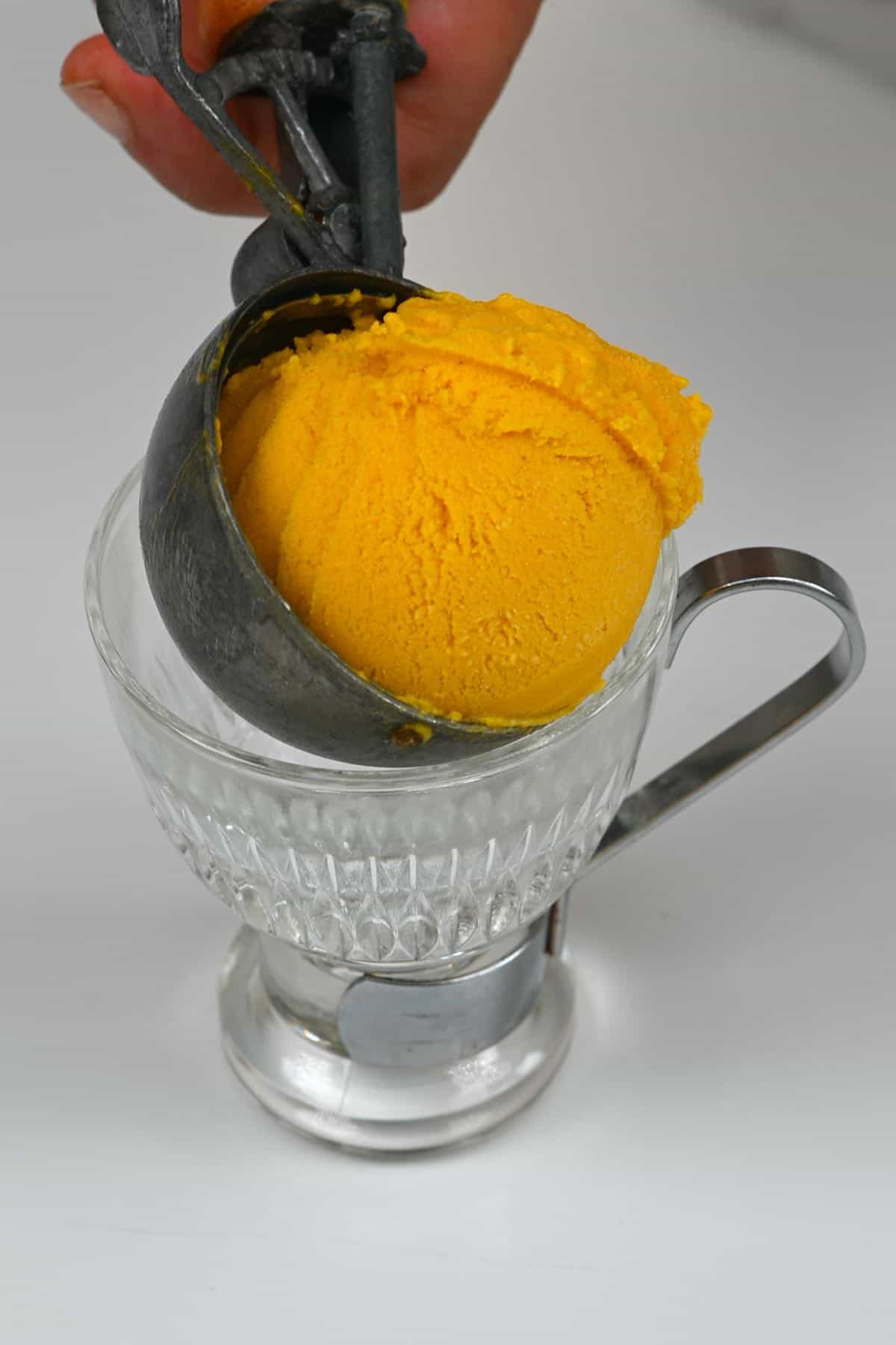 A scoop of mango ice cream being placed in a cup
