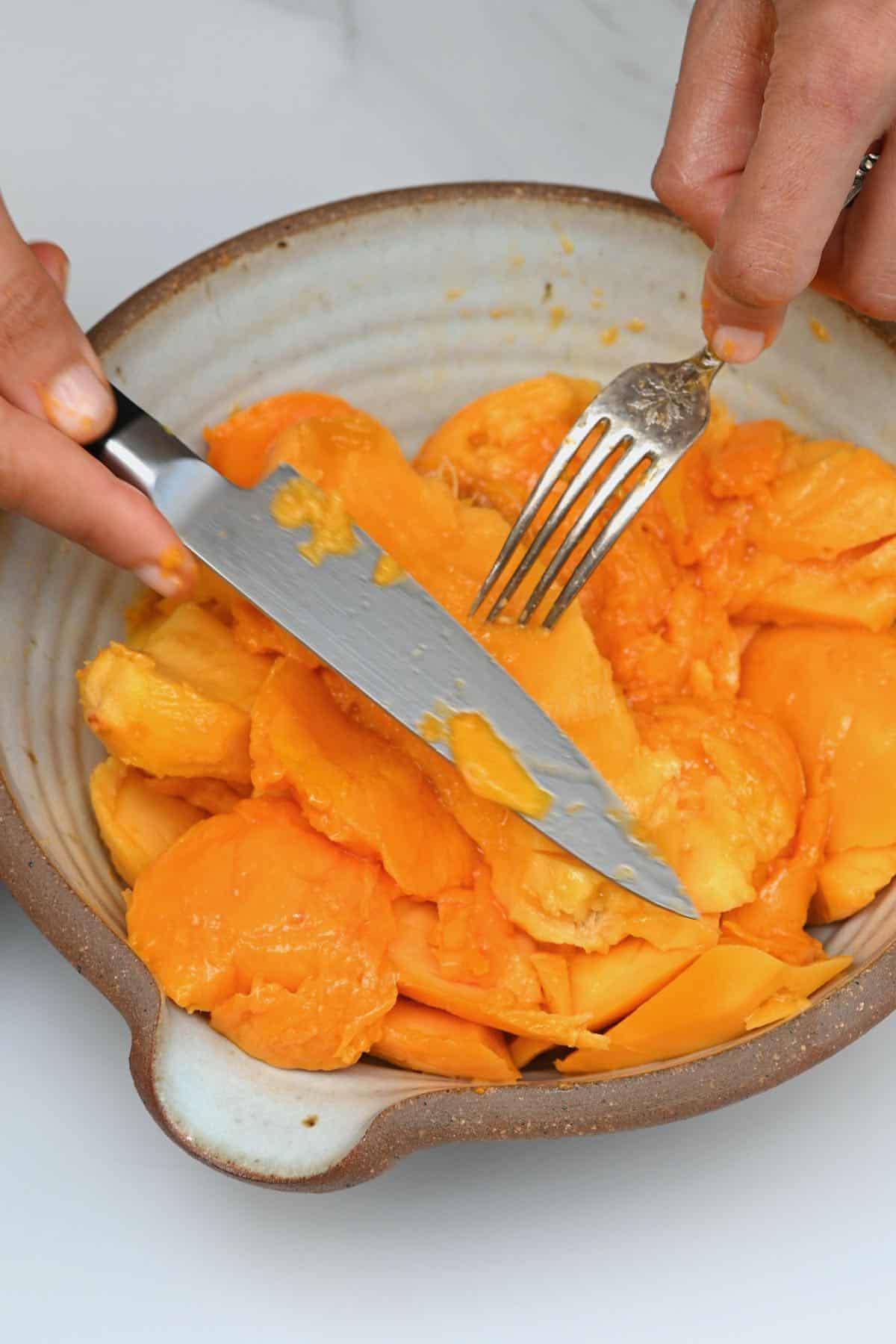 Cutting off mango flesh