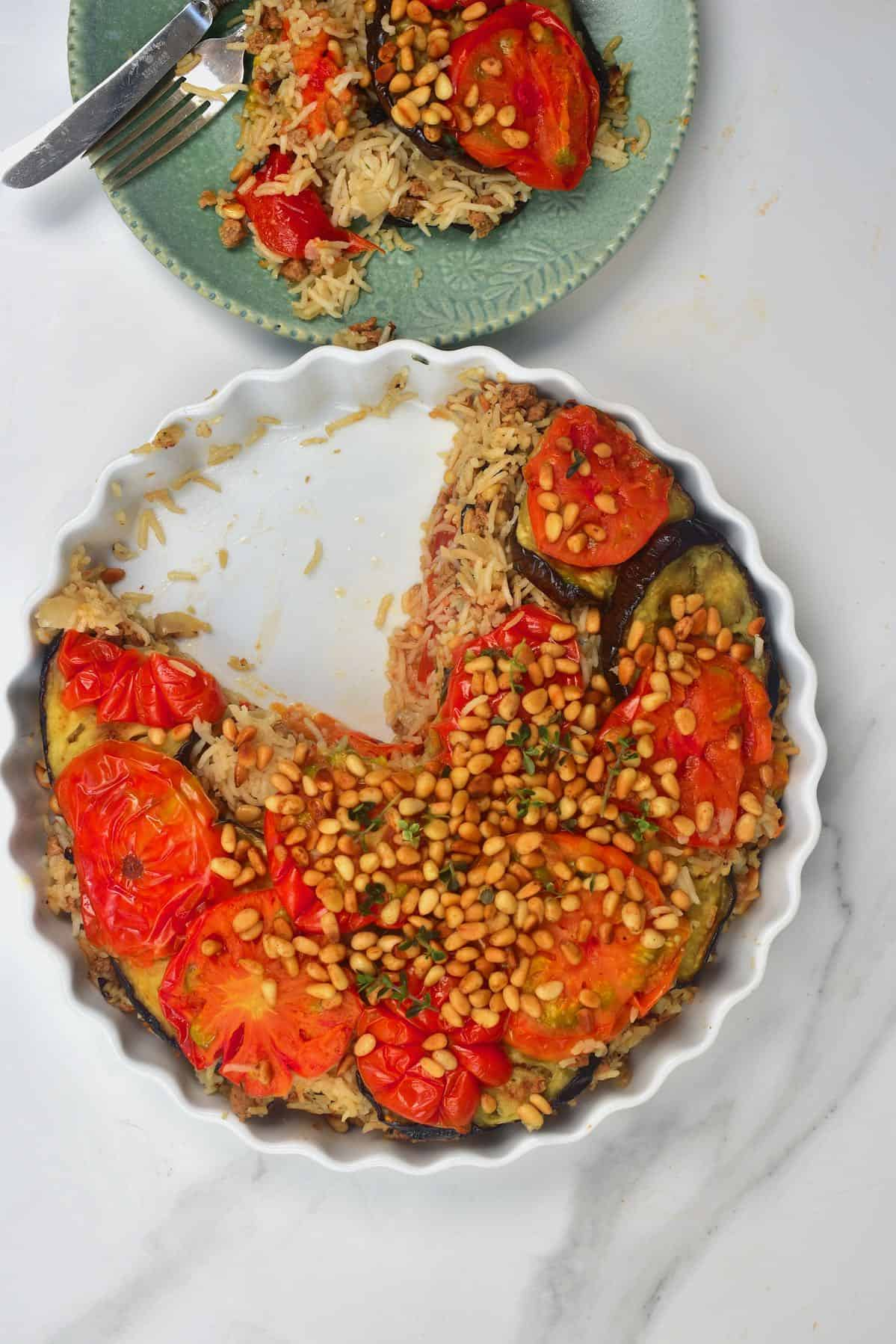 Maqluba in a baking dish with a slice cut off