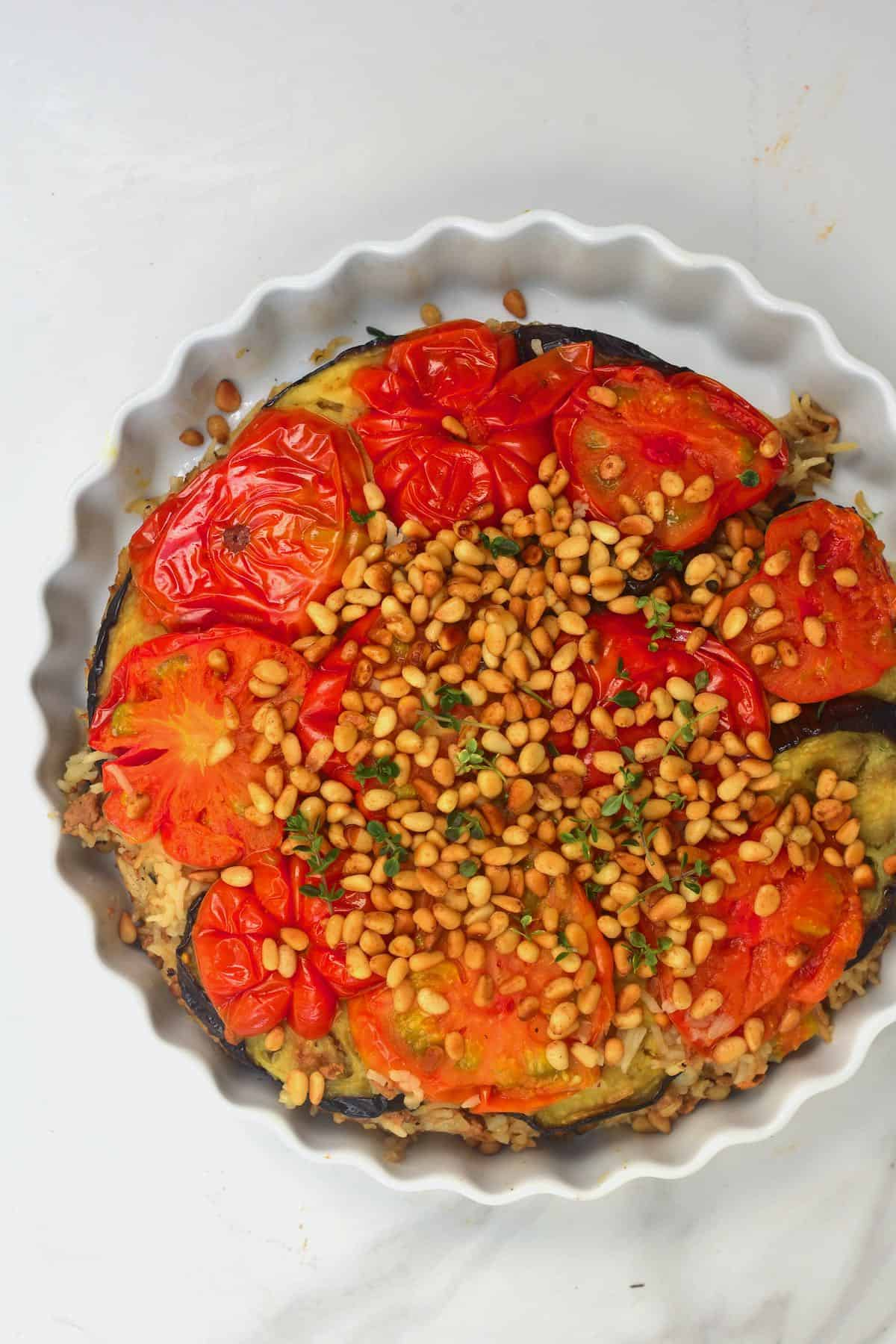 Maqluba topped with pine nuts