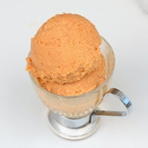 Two balls of peach ice cream in a small cup