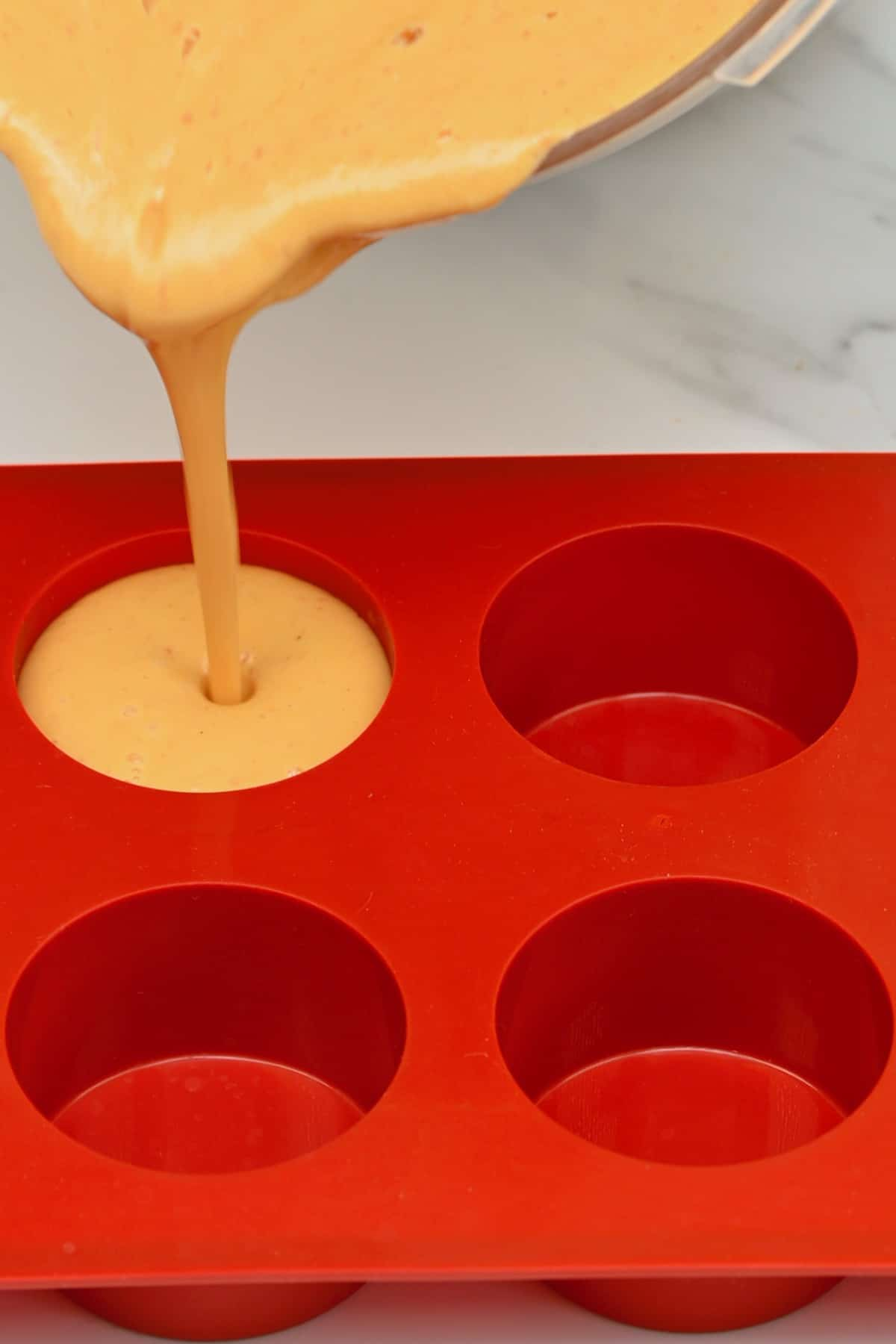 Pouring peach ice cream in an ice cube tray