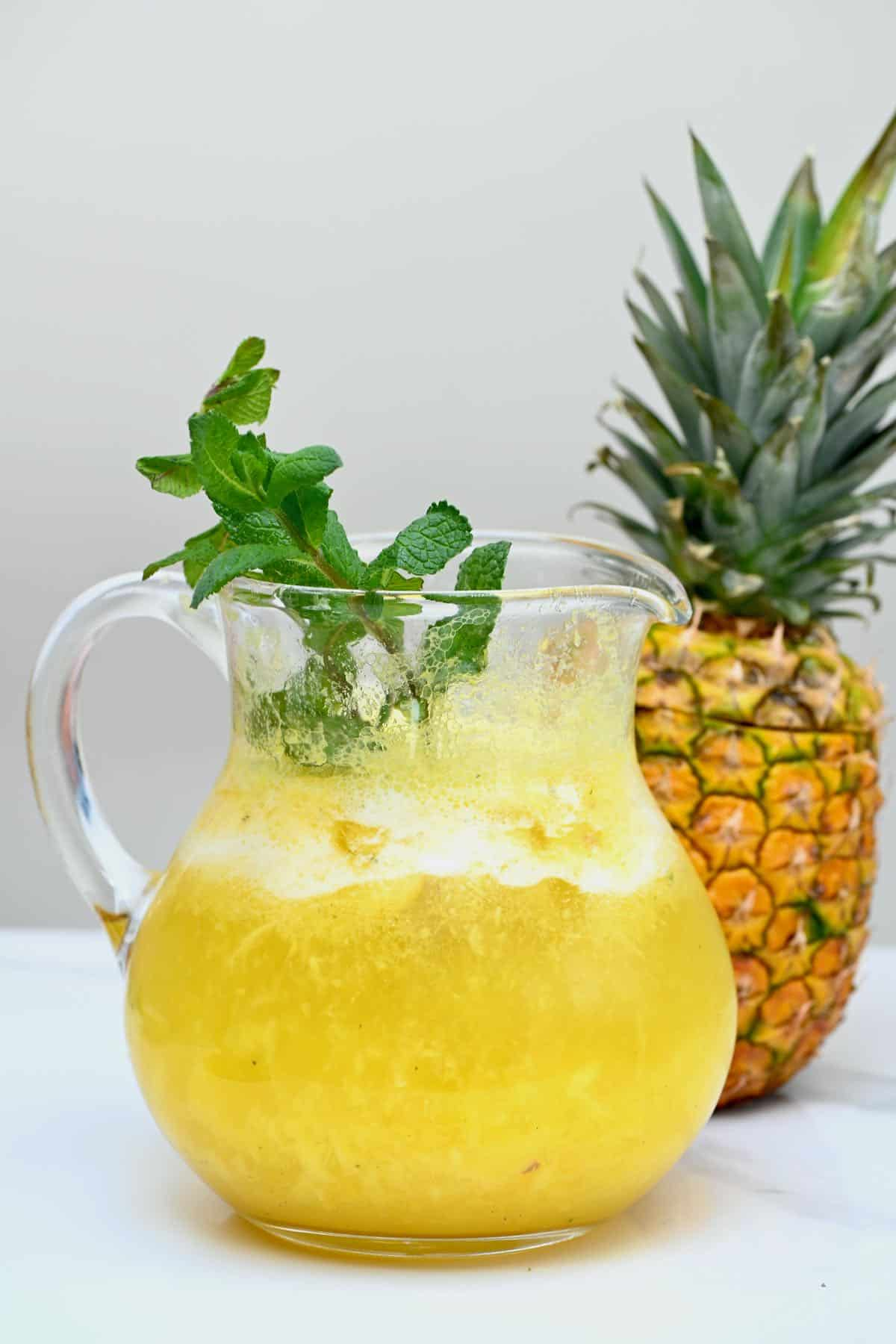 Pineapple lemonade served in a pitcher with mint leaves