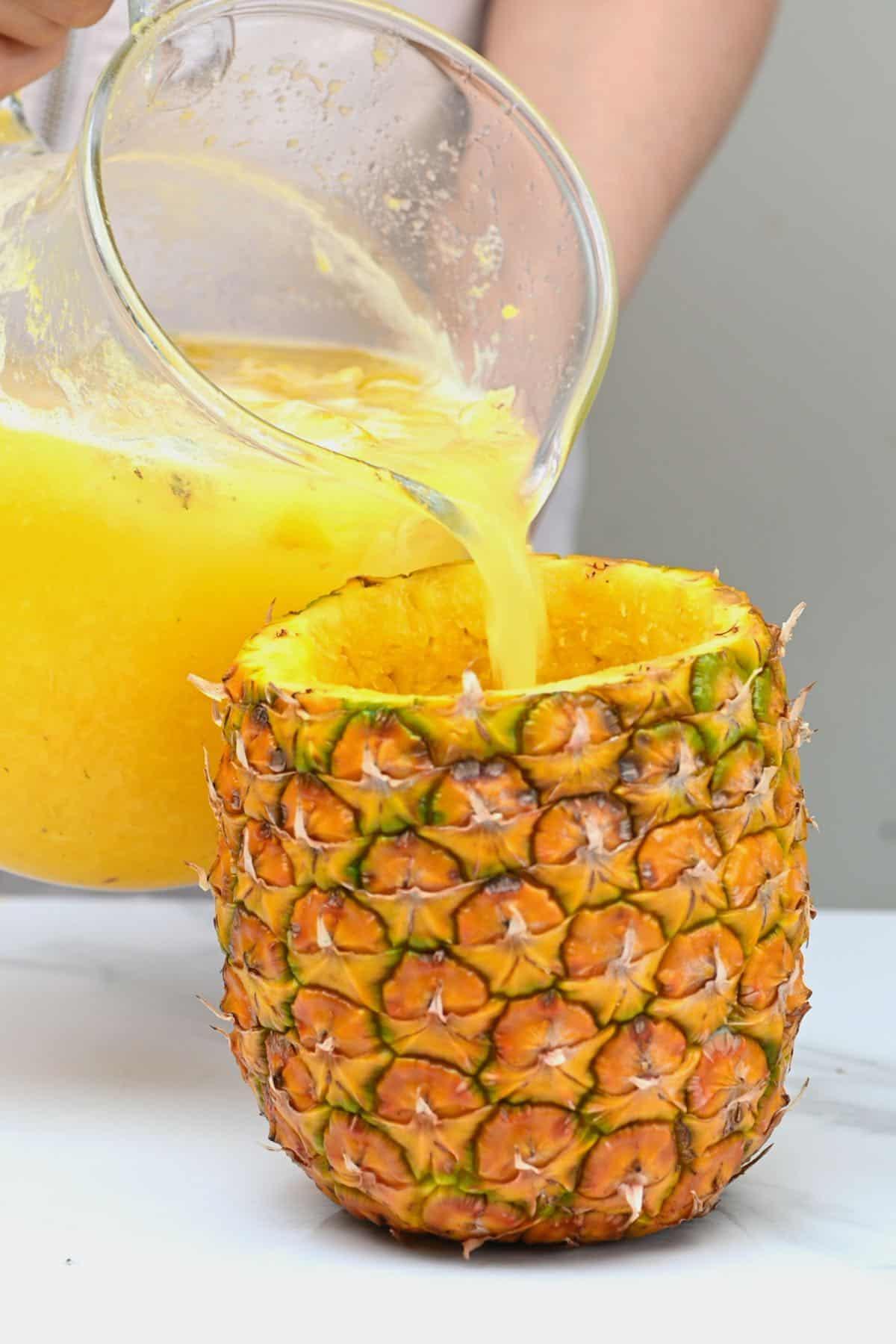 Pouring pineapple lemonade in a pineapple shell